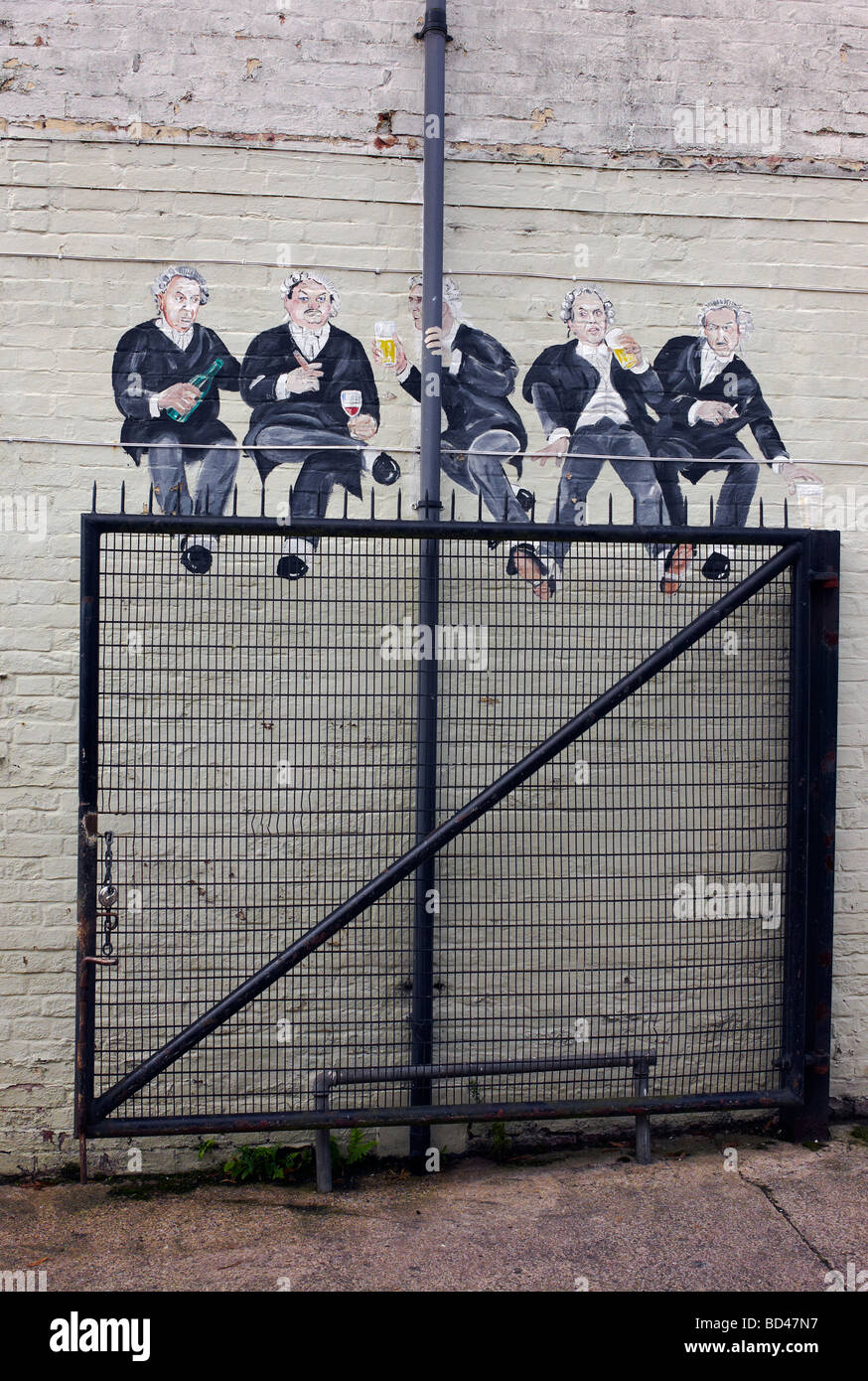 A mural of lawyers seemingly sitting on a gate at the back of the Tilted Wig pub in Warwick, UK - Stock Image