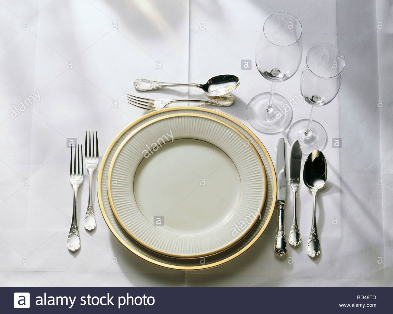 Table setting: gold-rim plates, cutlery, fish cutlery, glasses Stock ...