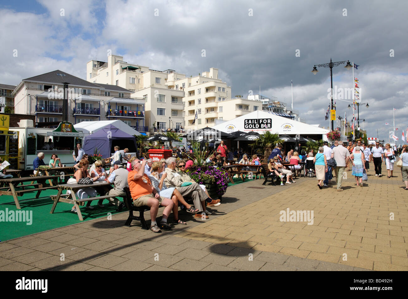 Cowes regatta week visitors relaxing on The Parade a waterfront area of catering bars and food outlet tents Isle Stock Photo