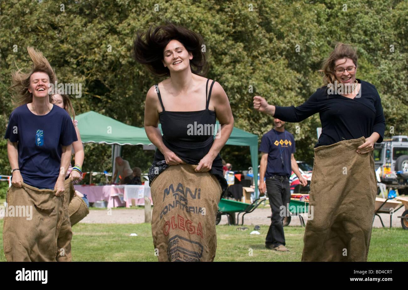 Women taking part in sack race at Oakhanger Village Show, Hampshire, UK. - Stock Image
