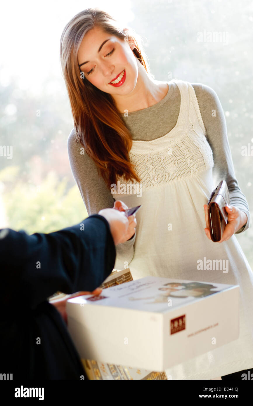 woman receiving a pair of shoes from a delivery man - Stock Image