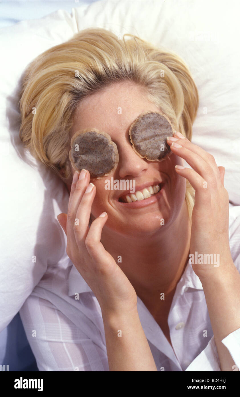 woman with tea bags on her eyes to ease puffiness - Stock Image