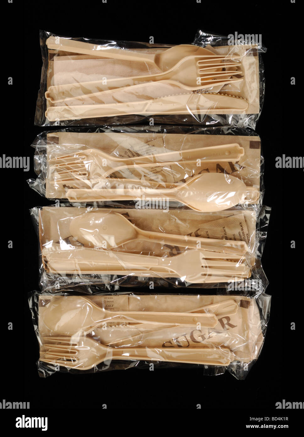 Four plastic bags with eating utensils on a black background - Stock Image