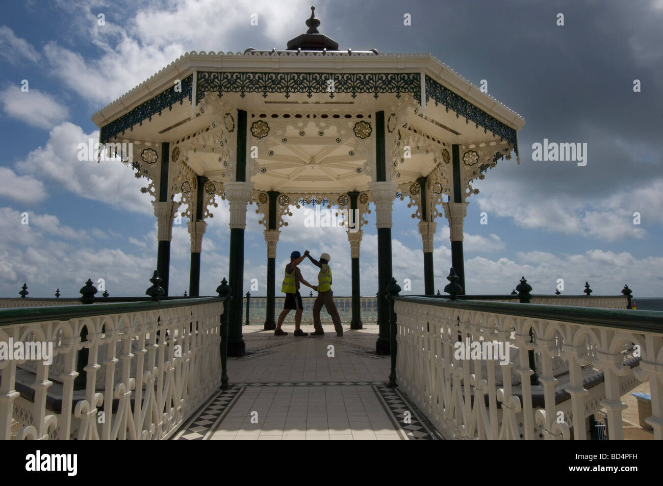 Two burly builders in hard hats and safety vests dance to celebrate the million pound refurbishment of Brighton - Stock Image