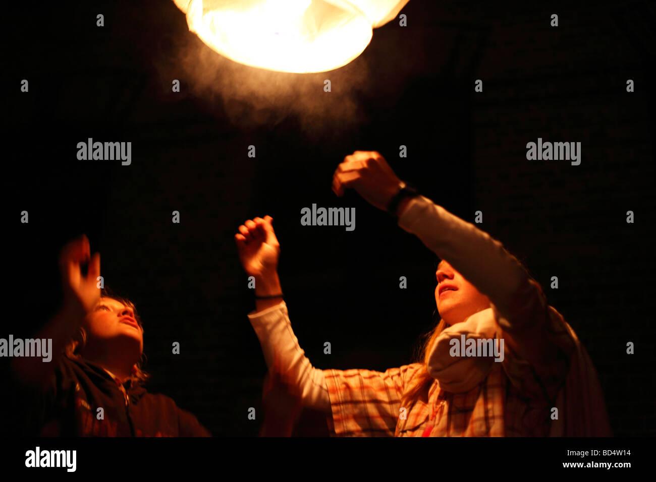 teens launch sky lantern; hot air balloon; floating lantern - Stock Image