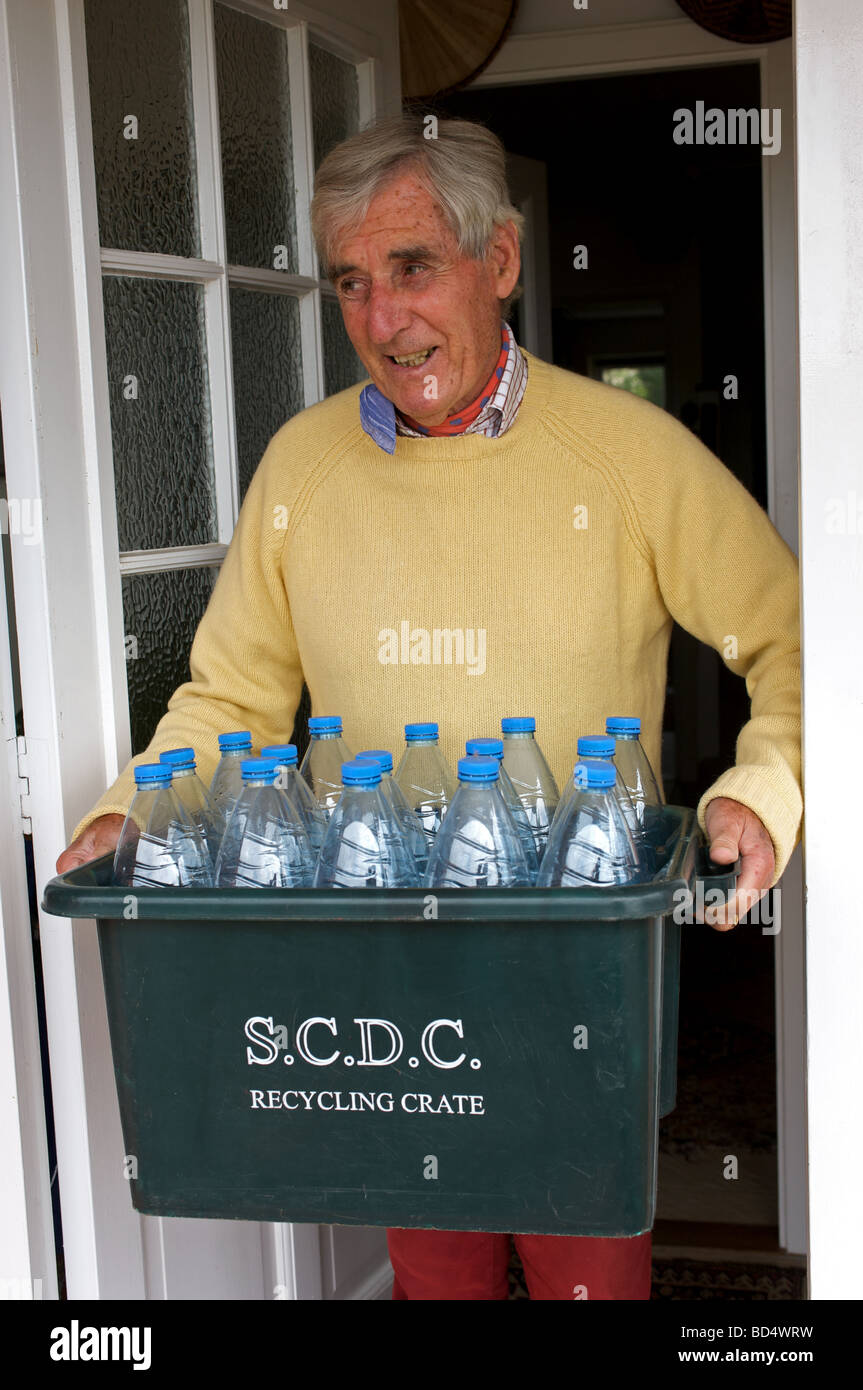 Homeowner recycling plastic water bottles placed in Suffolk Coastal District Council recycling crete - Stock Image