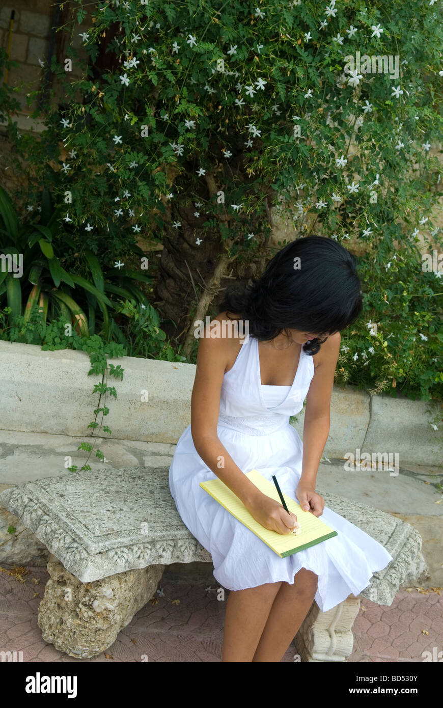 Young woman writing a letter in the garden - Stock Image