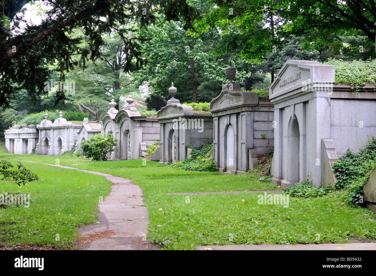 Row of old granite stone mausoleums in cemetery - Stock Image