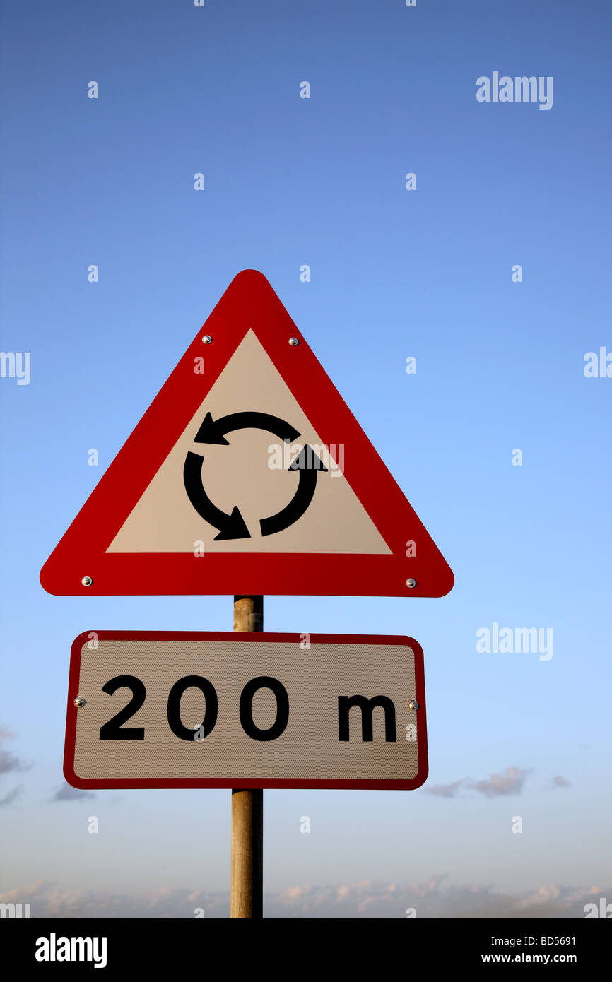 Traffic sign indicating a roundabout 200m ahead against a blue sky with copy space. - Stock Image