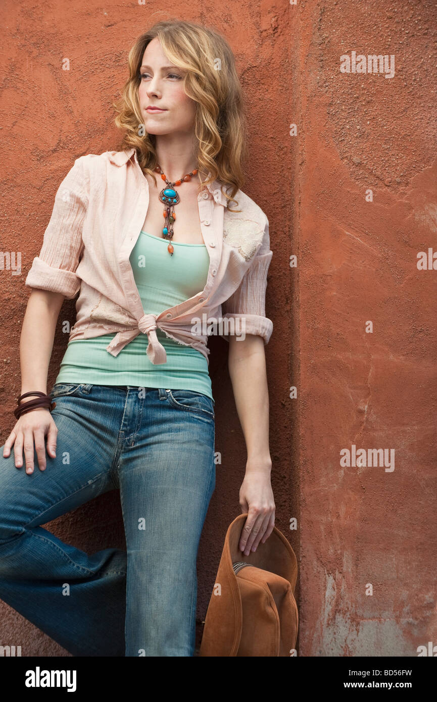 A woman outdoors leaning on a wall - Stock Image