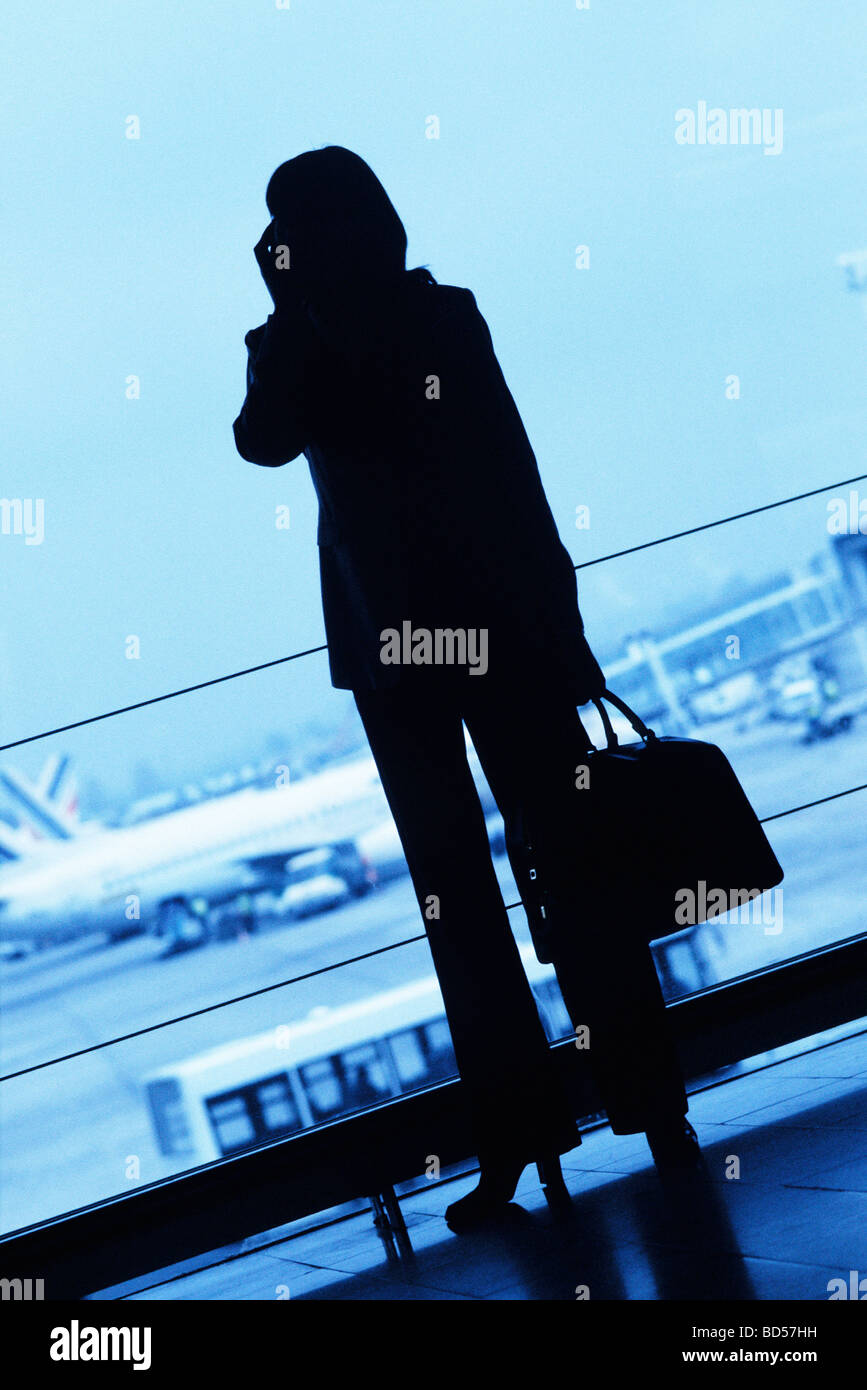 e8e5fad6 Silhouette of woman traveler using cell phone, holding travel bag in  airport - Stock Image