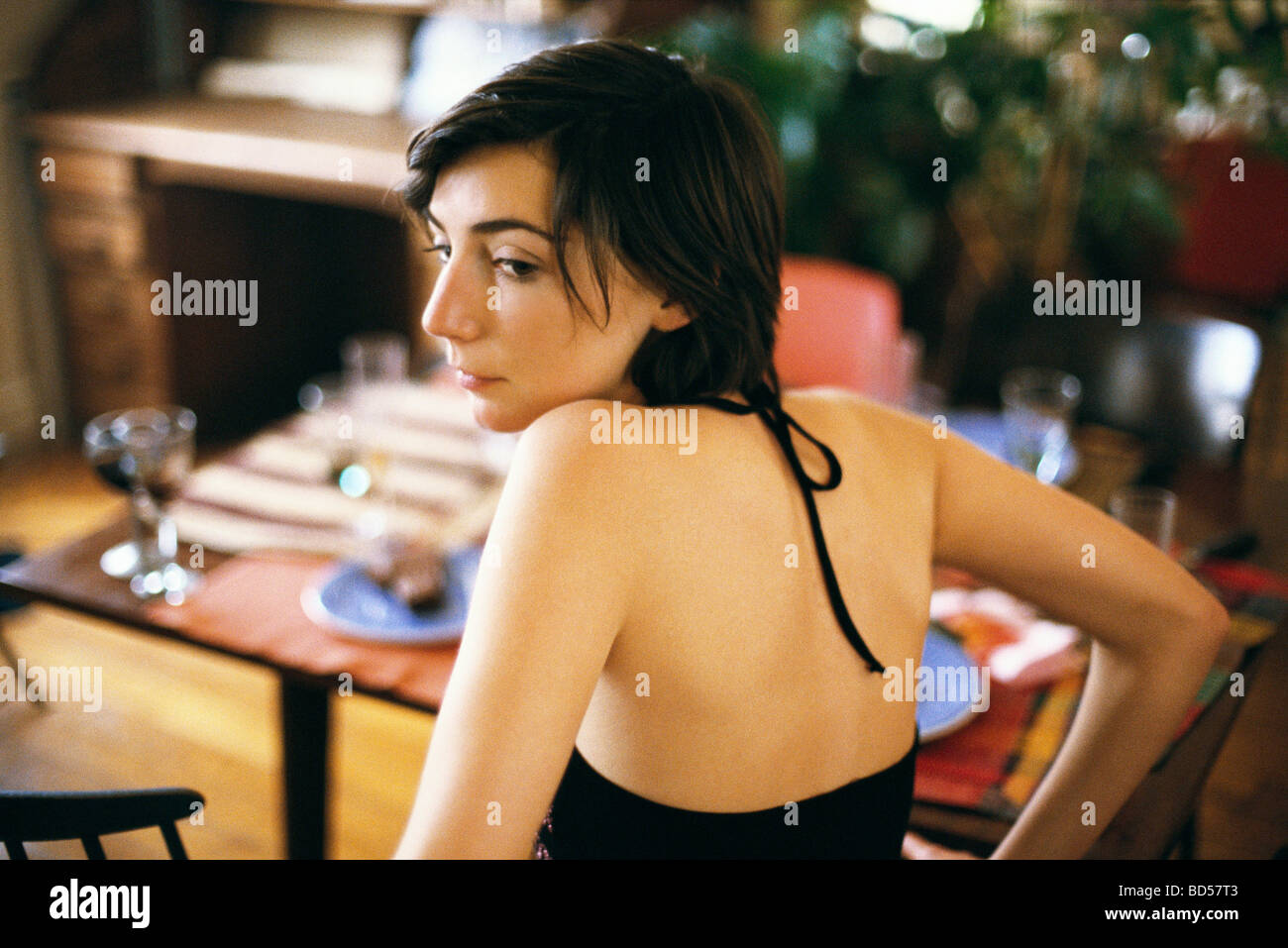 Woman looking over shoulder contemplatively looking away, set table in background - Stock Image