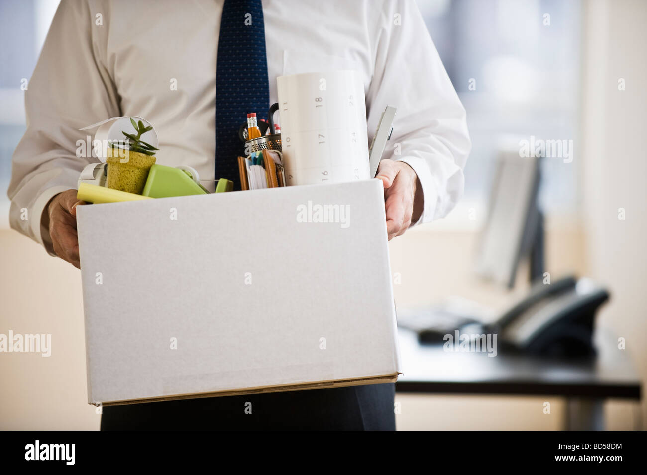 A businessman with a box full of desk stuff - Stock Image