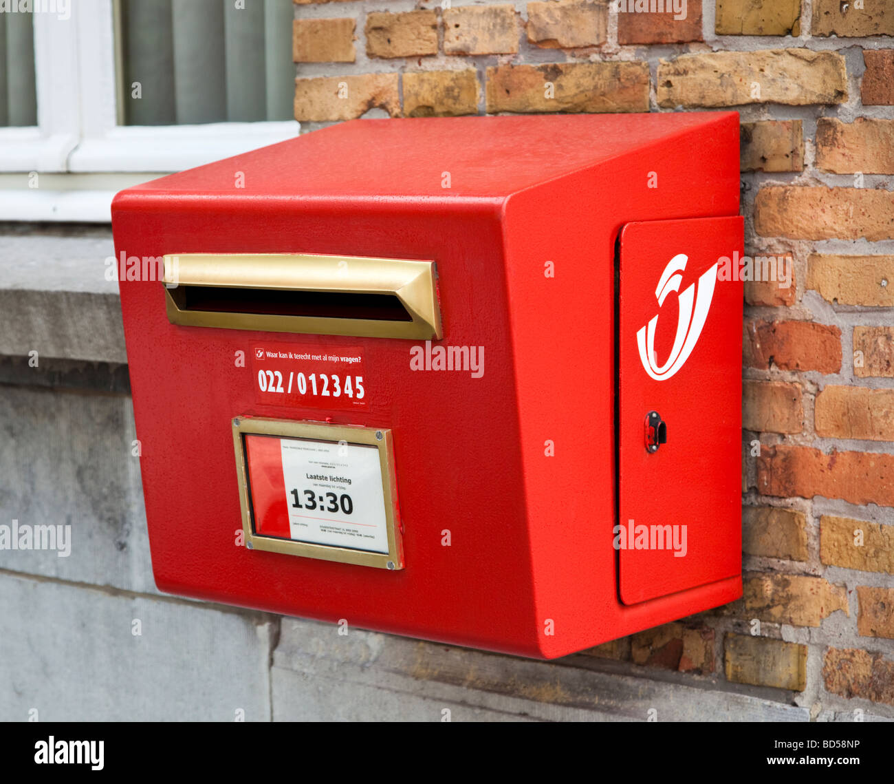 Postbox with collection time in Belgium, Europe - Stock Image