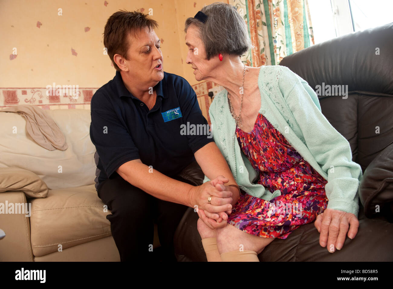 Care worker helps a woman suffering from Alzheimer's disease in her  home - Stock Image