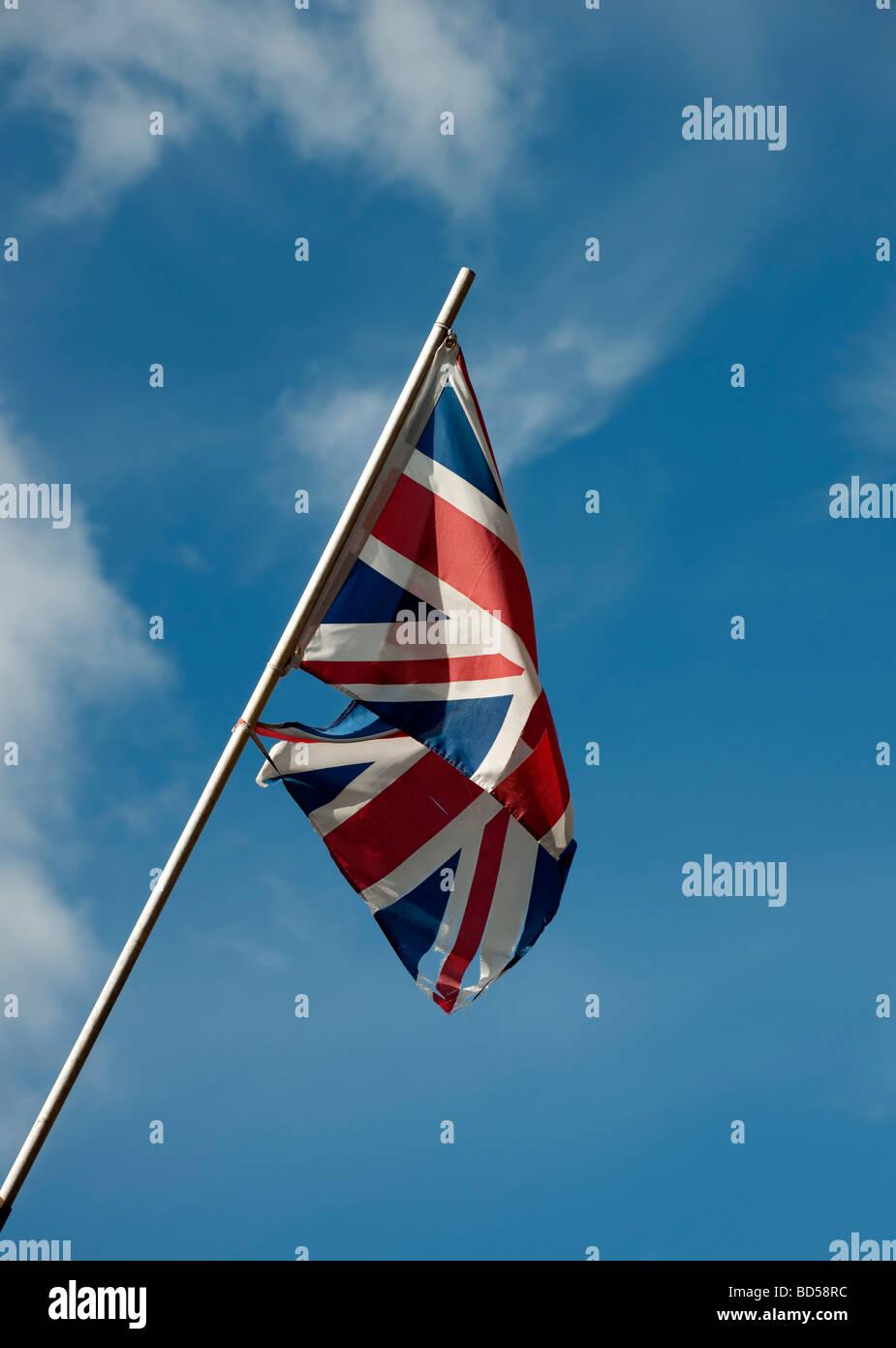 Union Flag flying on pole against blue sky - Stock Image