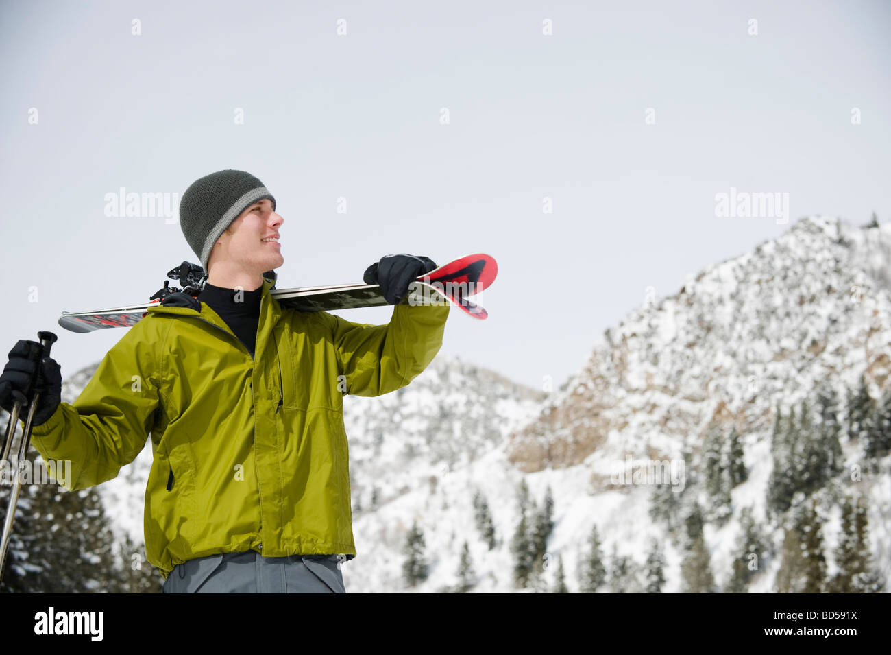 A downhill skier carrying skis - Stock Image