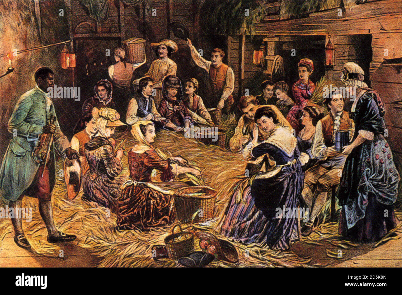 RURAL CORNHUSKING  in 18th century America with musician at left - Stock Image