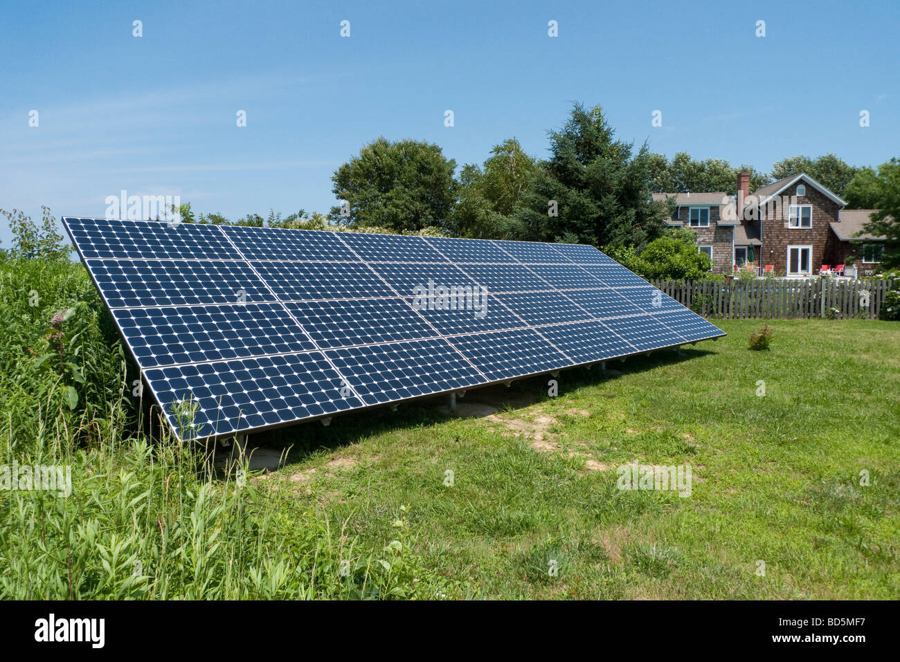 SunPower solar energy panel with photovoltaic cell grid installed. Home that it helps power is in the background. - Stock Image