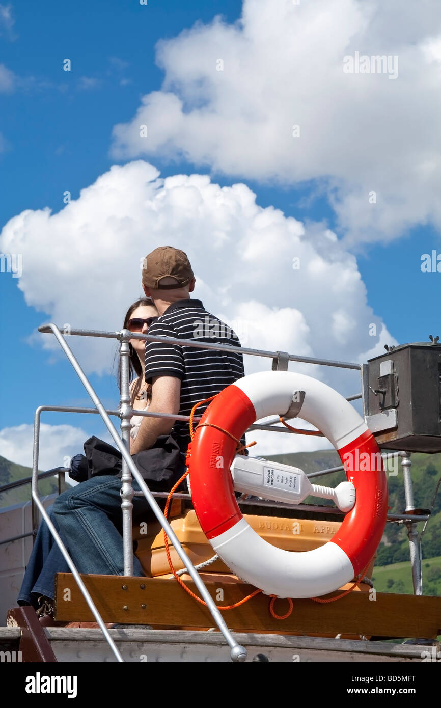 A lifebelt on a ferry with passengers in the background. - Stock Image