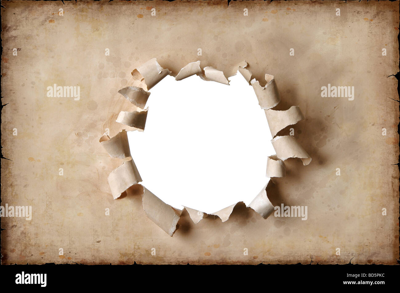 Vintage paper with a hole torn in the middle - Stock Image