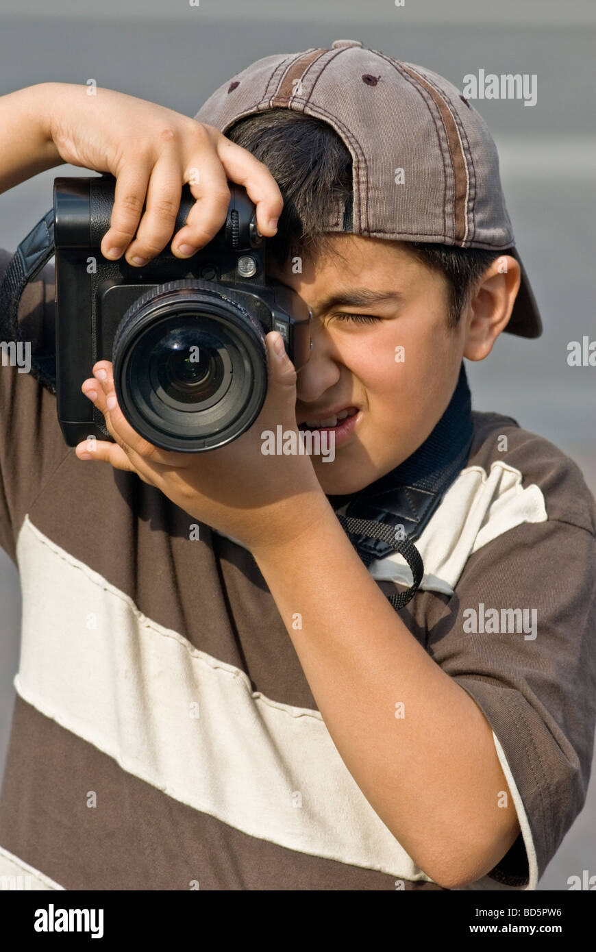 BOY IN HIS 10s TAKING PICTURE WITH PROFESSIONAL CAMERA - Stock Image