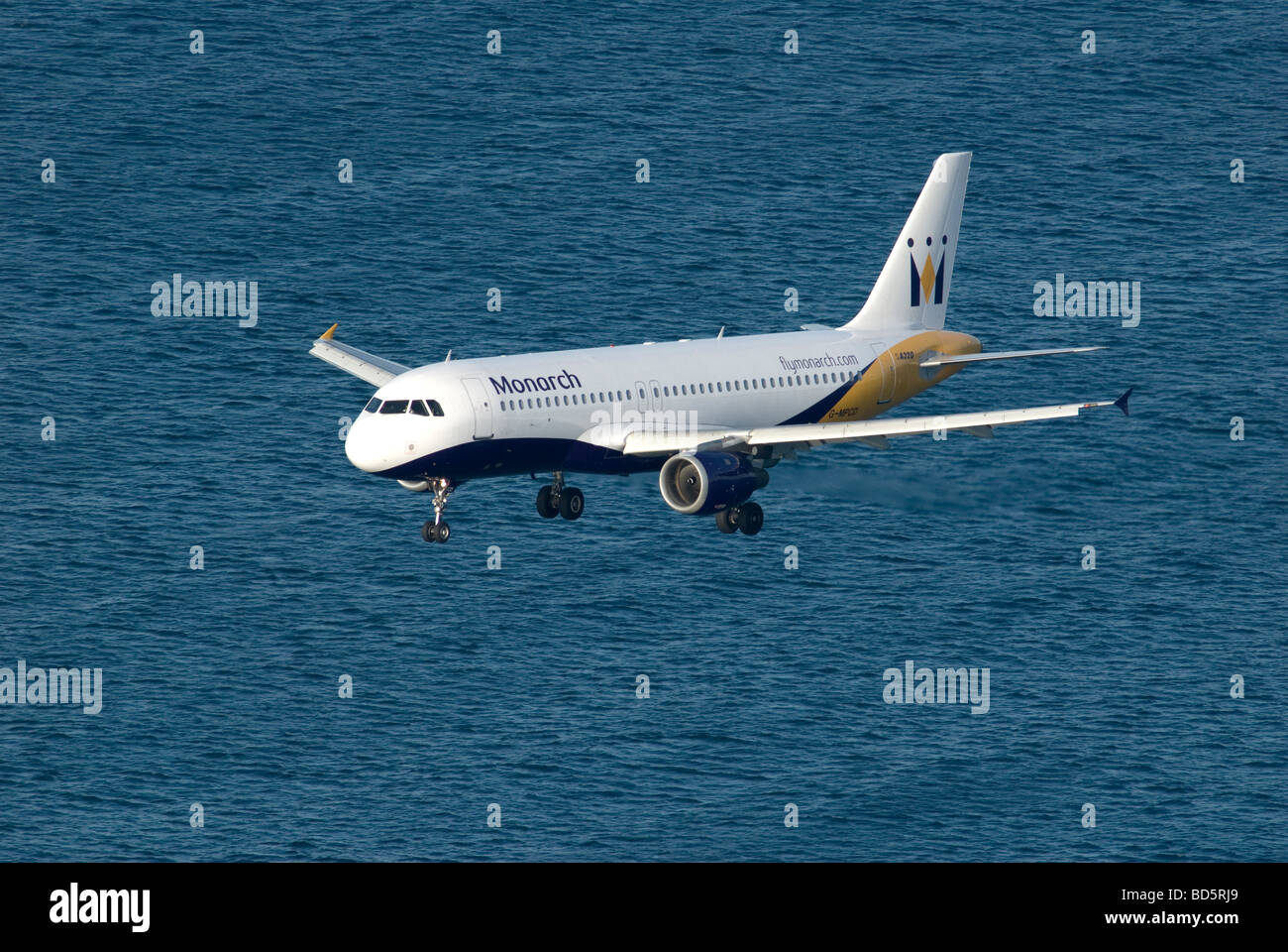 Monarch airlines jet on final approach to Gibraltar over Mediterranean sea - Stock Image