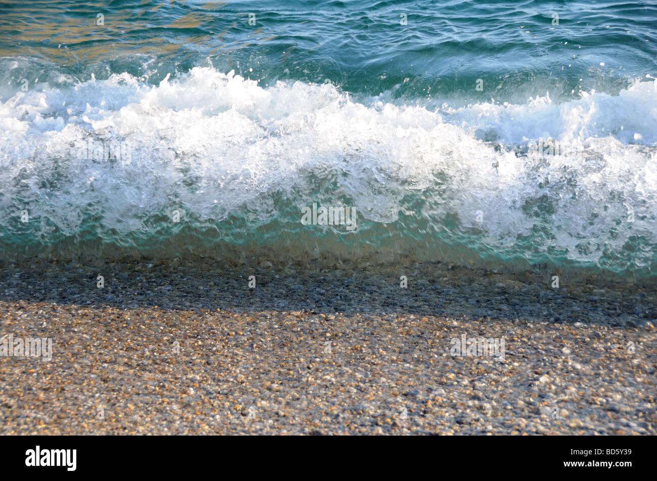 Breaking wave on shingle beach - Stock Image