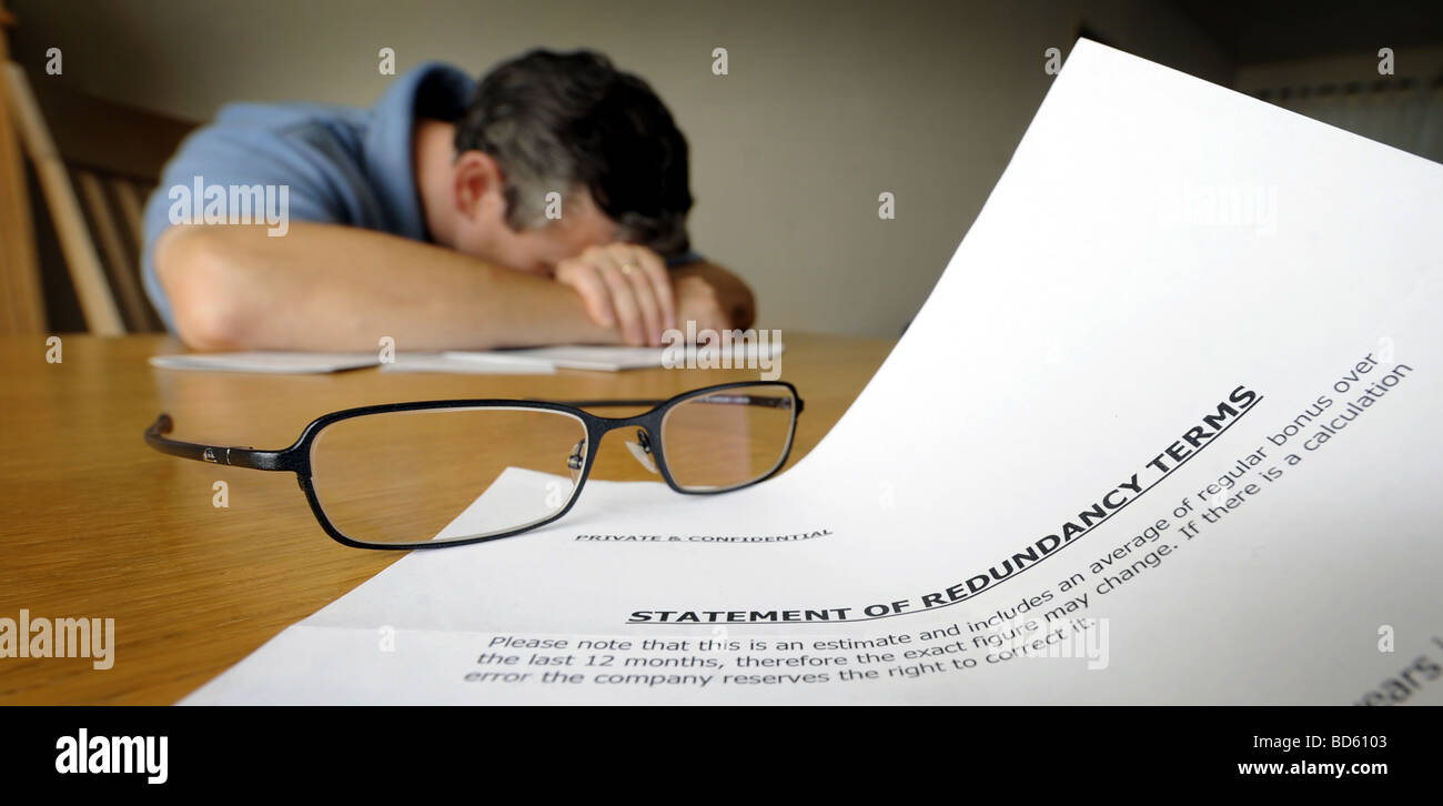 DISTRAUGHT MAN WITH LETTER SHOWING STATEMENT OF REDUNDANCY TERMS - Stock Image