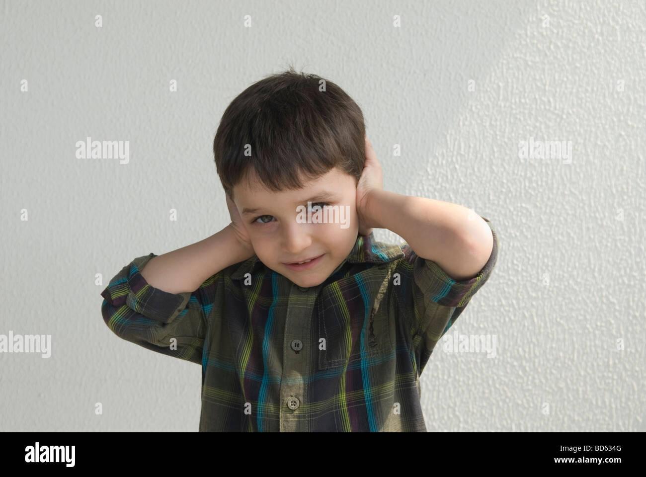 Little boy hands over ears - Stock Image