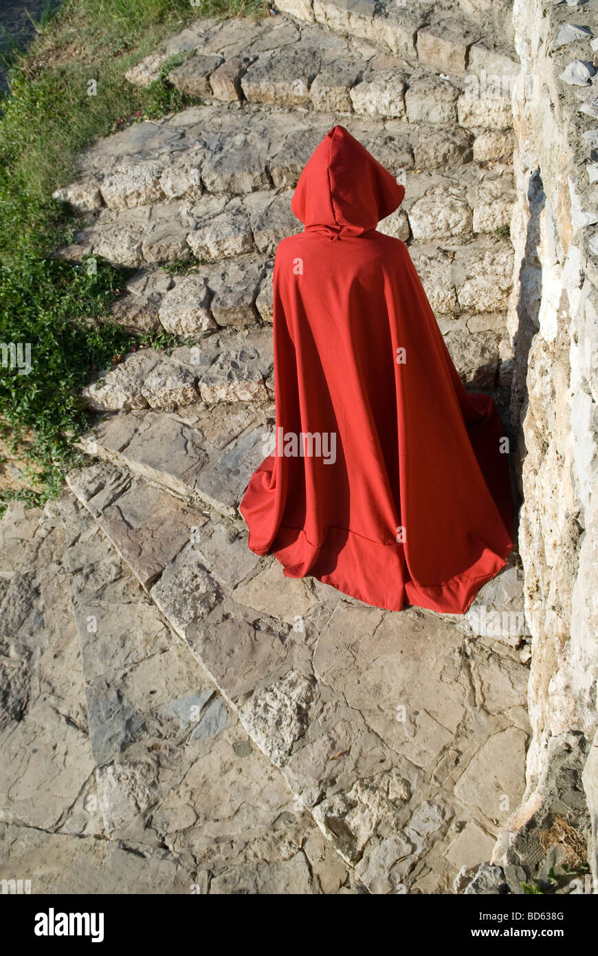 Mysterious figure in red cloak climbing down stone stairs Stock Photo