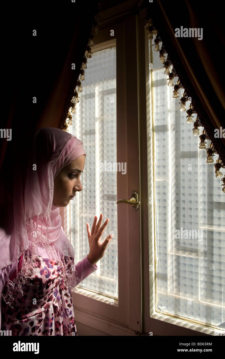 Young Muslim female by the window at home - Stock Image