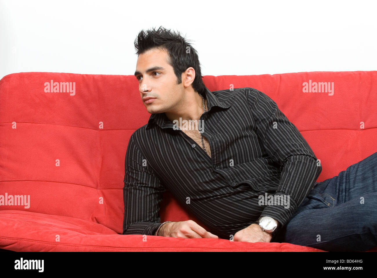 Young man sat on red sofa - Stock Image
