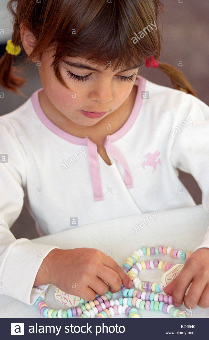 Small girl with candy necklace and candy watches - Stock Image