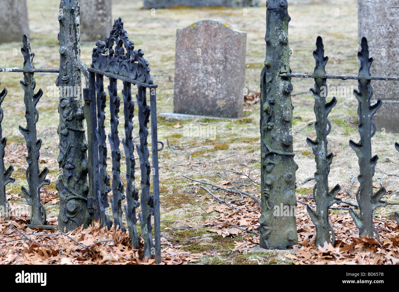 Cemetery plot with open wrought iron gate leading to grave plot and gravestones - Stock Image