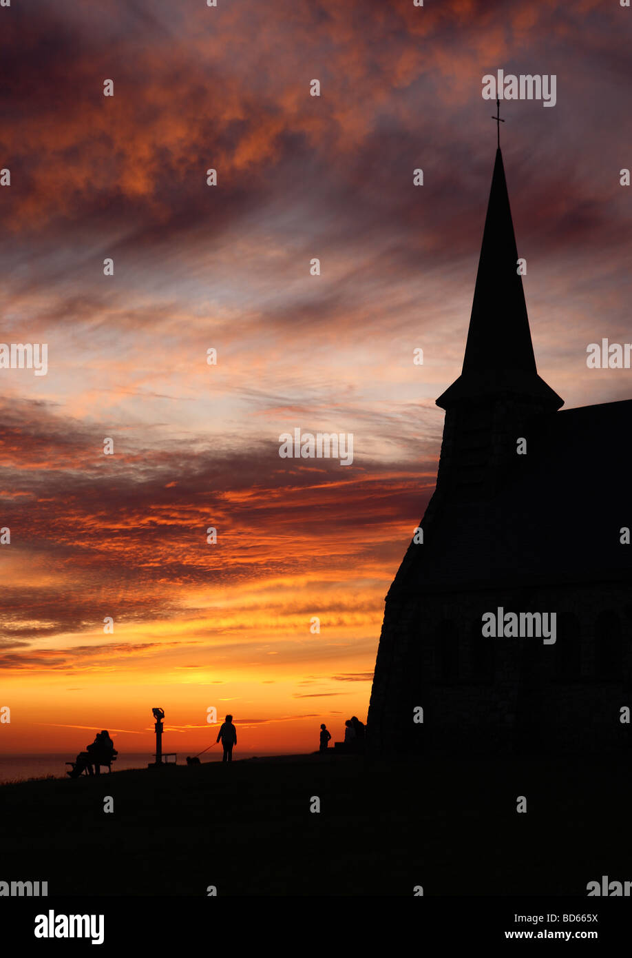 People watching the sun set adjacent to the chapel of Notre Dame in Etretat, Normandy, France, Europe - Stock Image