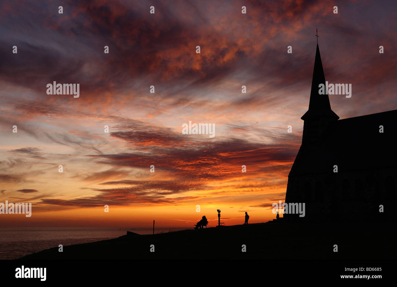 People watching the sun set adjacent to the church of Notre Dame in Etretat, France, Europe - Stock Image