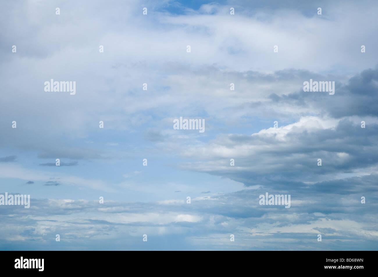 Soft misty cumulus and grey stratus Clouds, with a blue sky beyond. Stock Photo