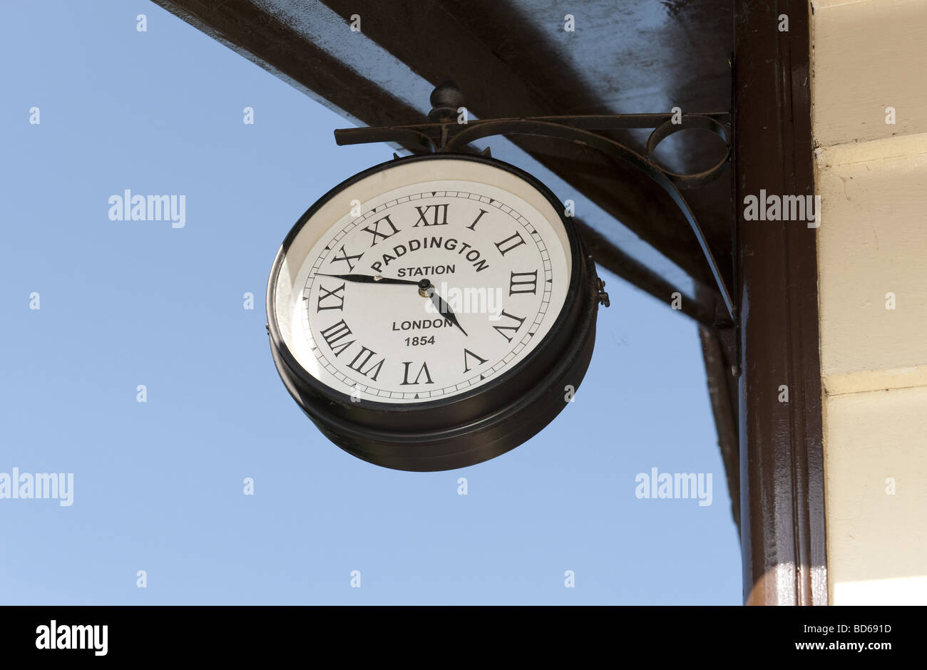 Wall hung Paddington Station branded analogue clock with Roman Numeral clock face indication 4.47 time against a - Stock Image