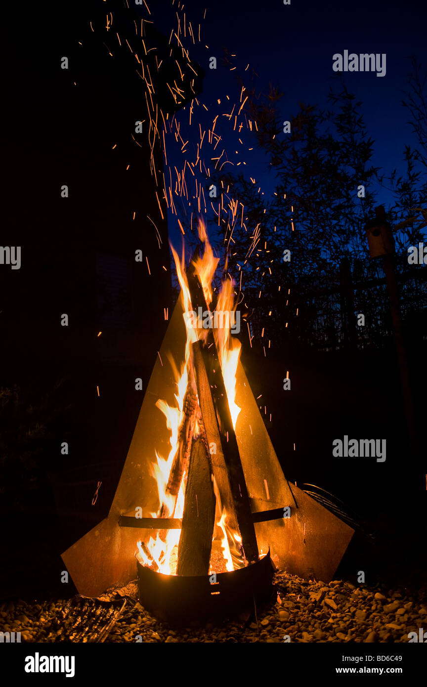 fire place in the garden summer evening night blue hot dark scenic romance romantic fireplace barbecue BBQ sky modern - Stock Image