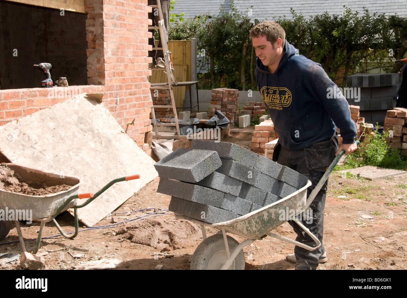 Man with wheelbarrow loaded with bricks - Stock Image