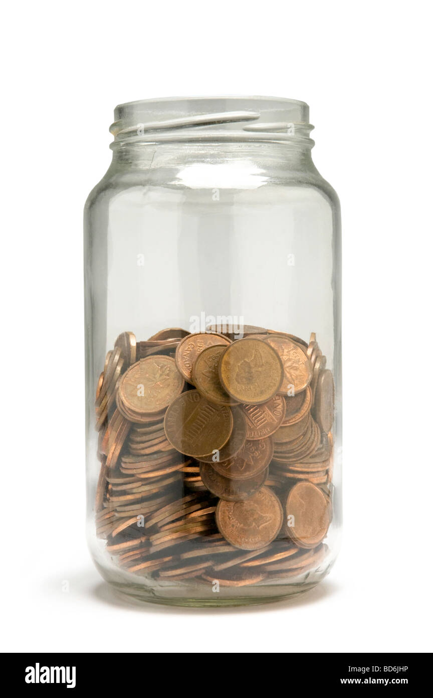 Penny coins being saved in glass jar - Stock Image