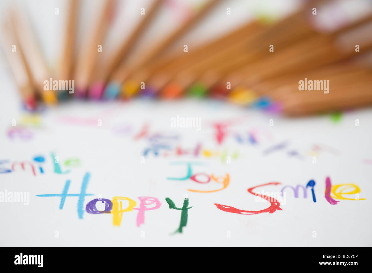 Coloured smile, happy, joy, fun words on paper with colouring pencils - Stock Image