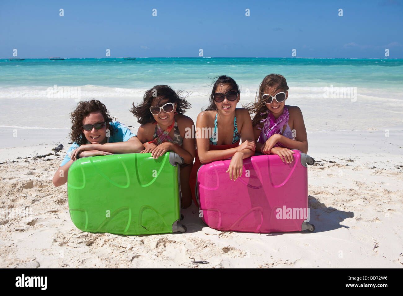 Four children sit behind their suitcases on the beach - Stock Image