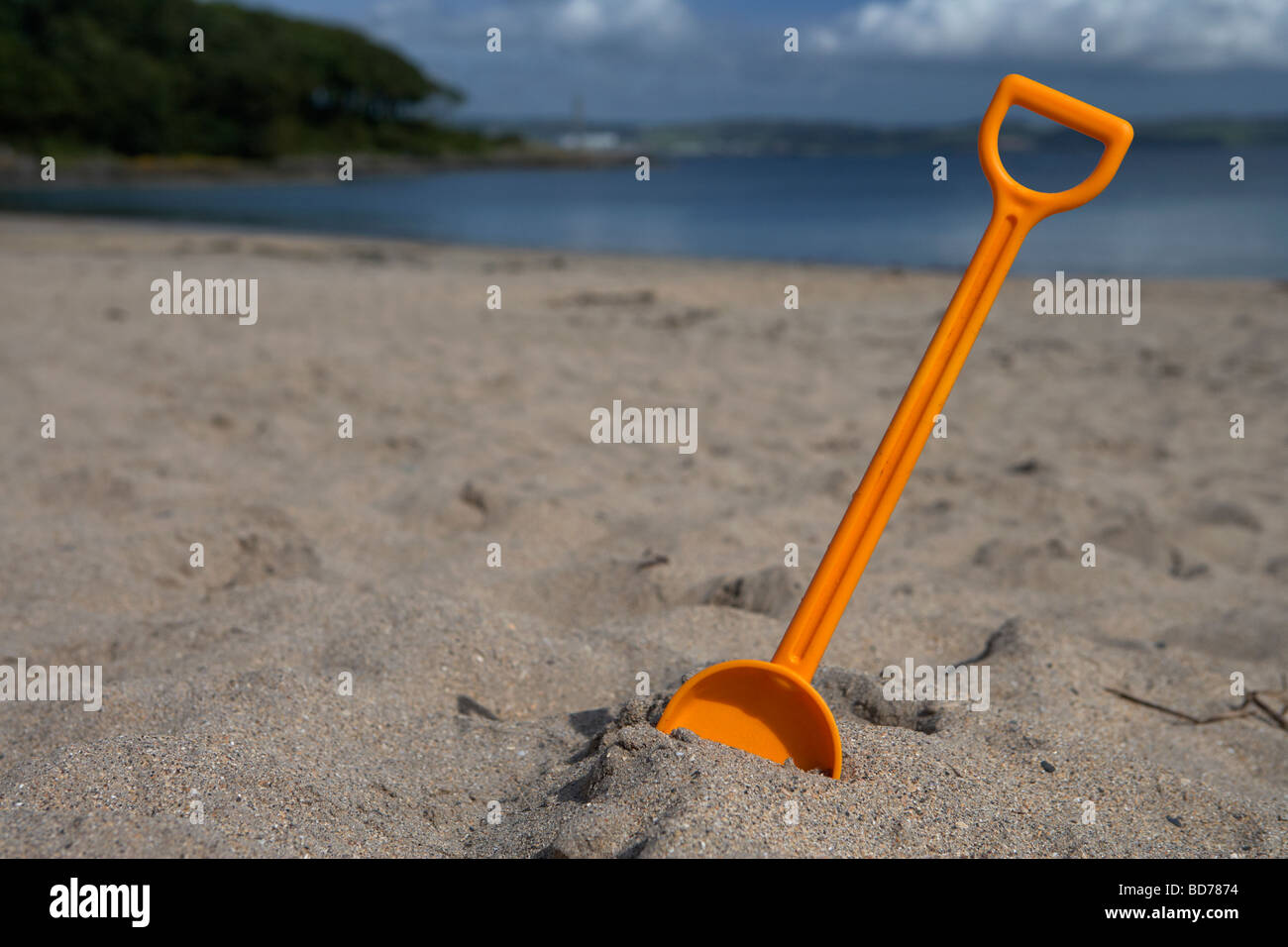 childs toy plastic spade stuck into the sand on a beach in the uk - Stock Image