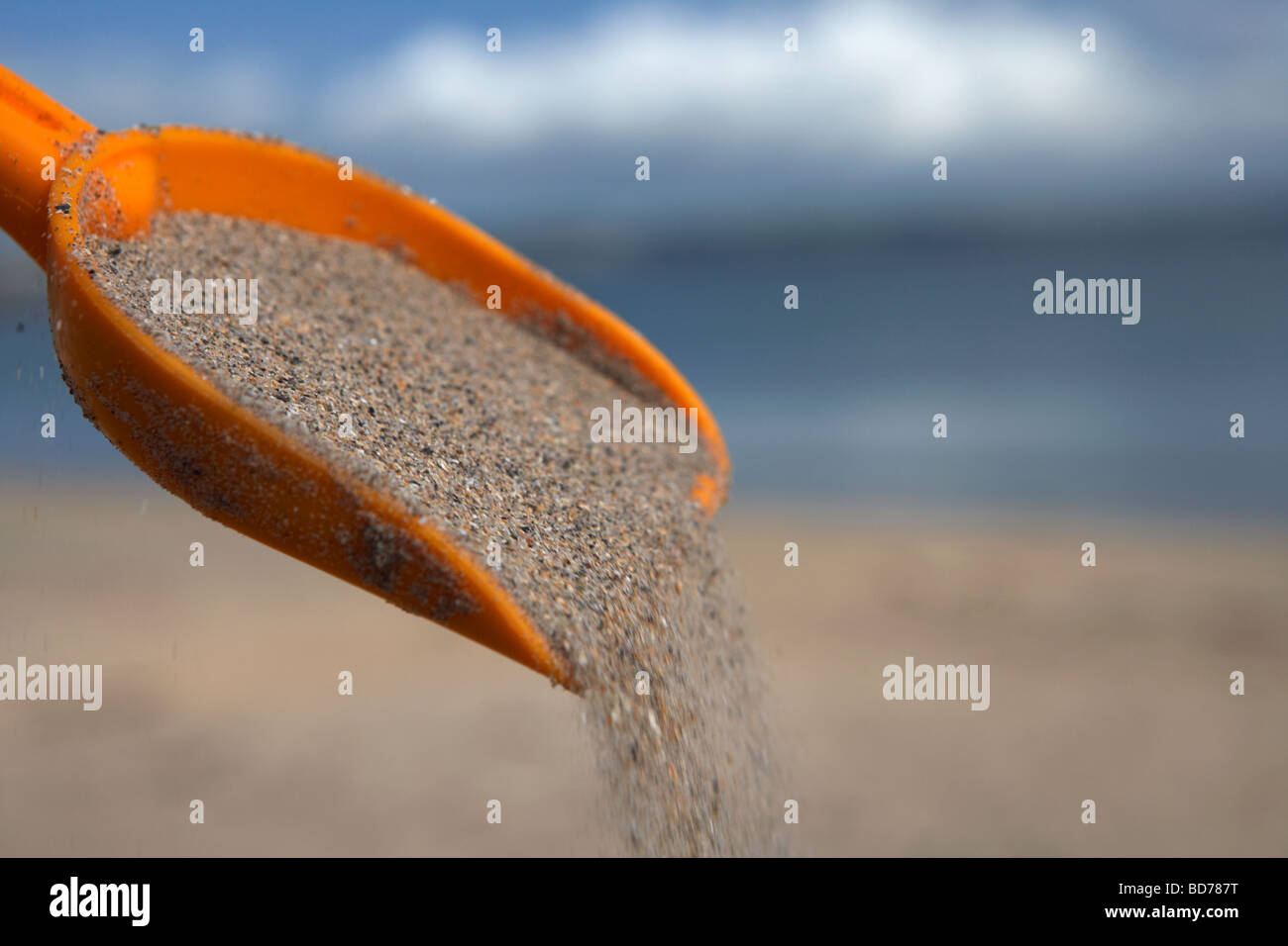grains of sand flowing off a childs toy plastic spade on a beach in the uk - Stock Image