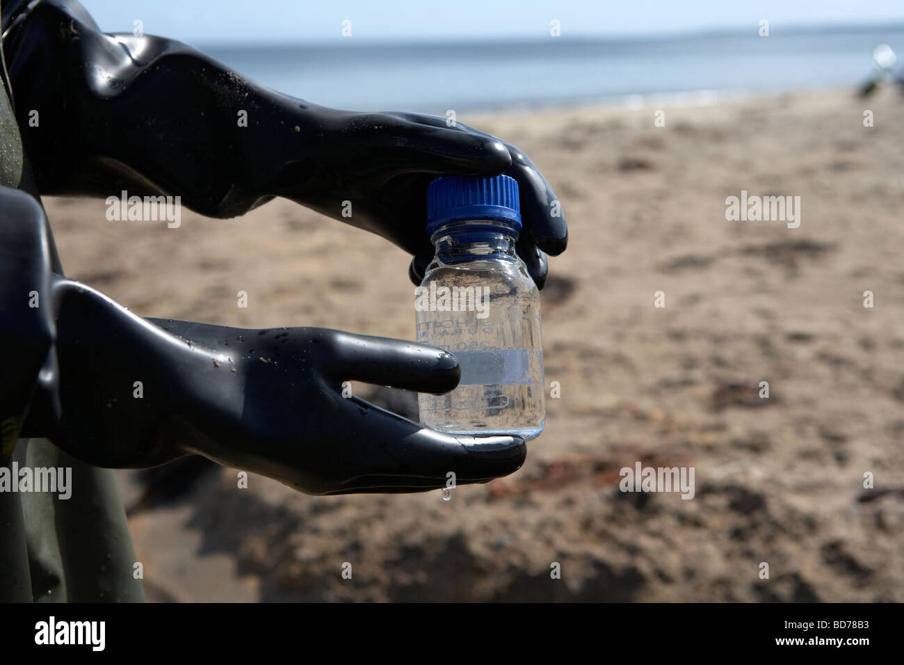 northern ireland environment service operative sampling water from local beach to assess water quality standards - Stock Image
