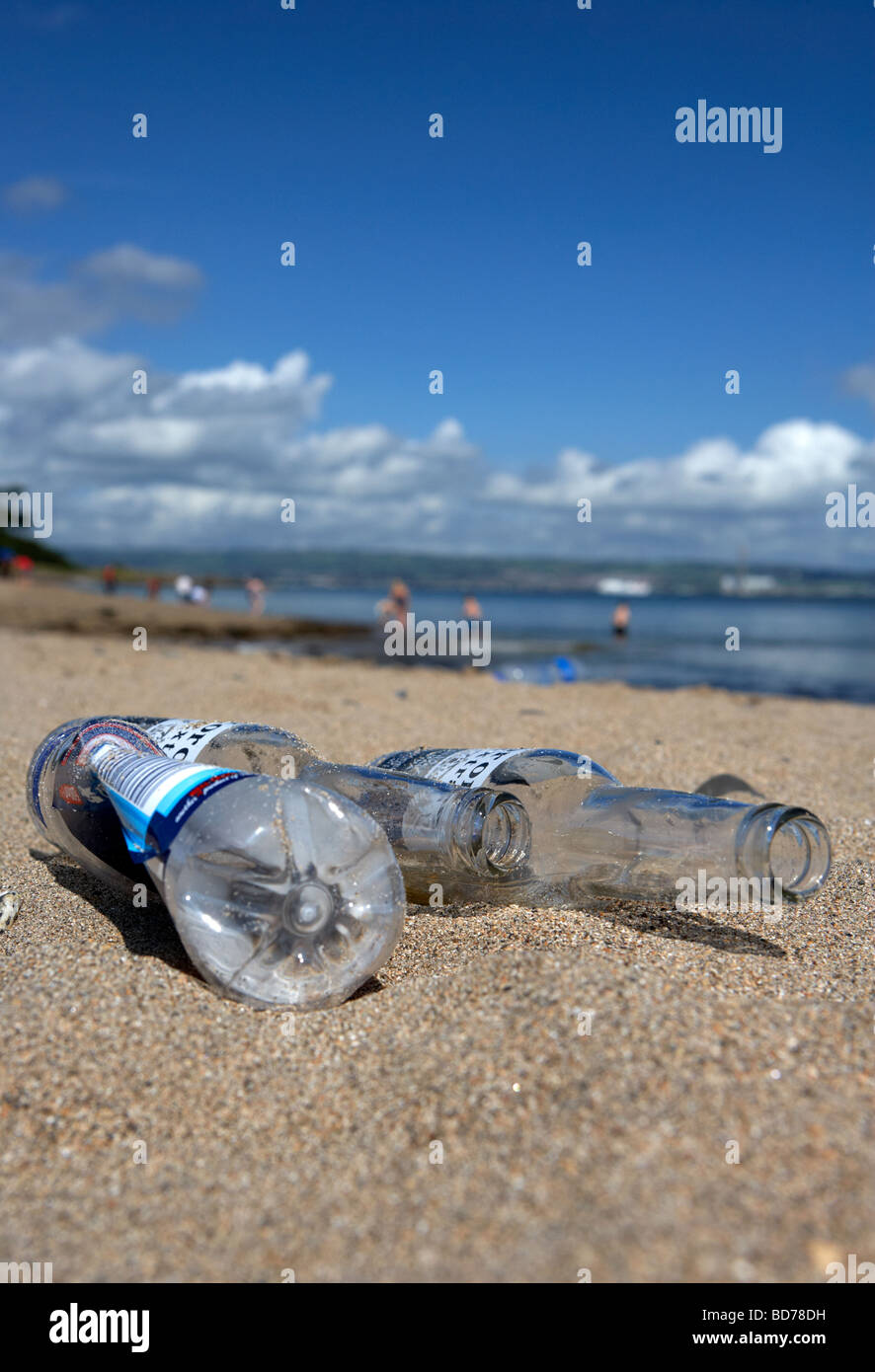empty beer bottles and plastic bottle discarded littering a beach in county down northern ireland uk - Stock Image