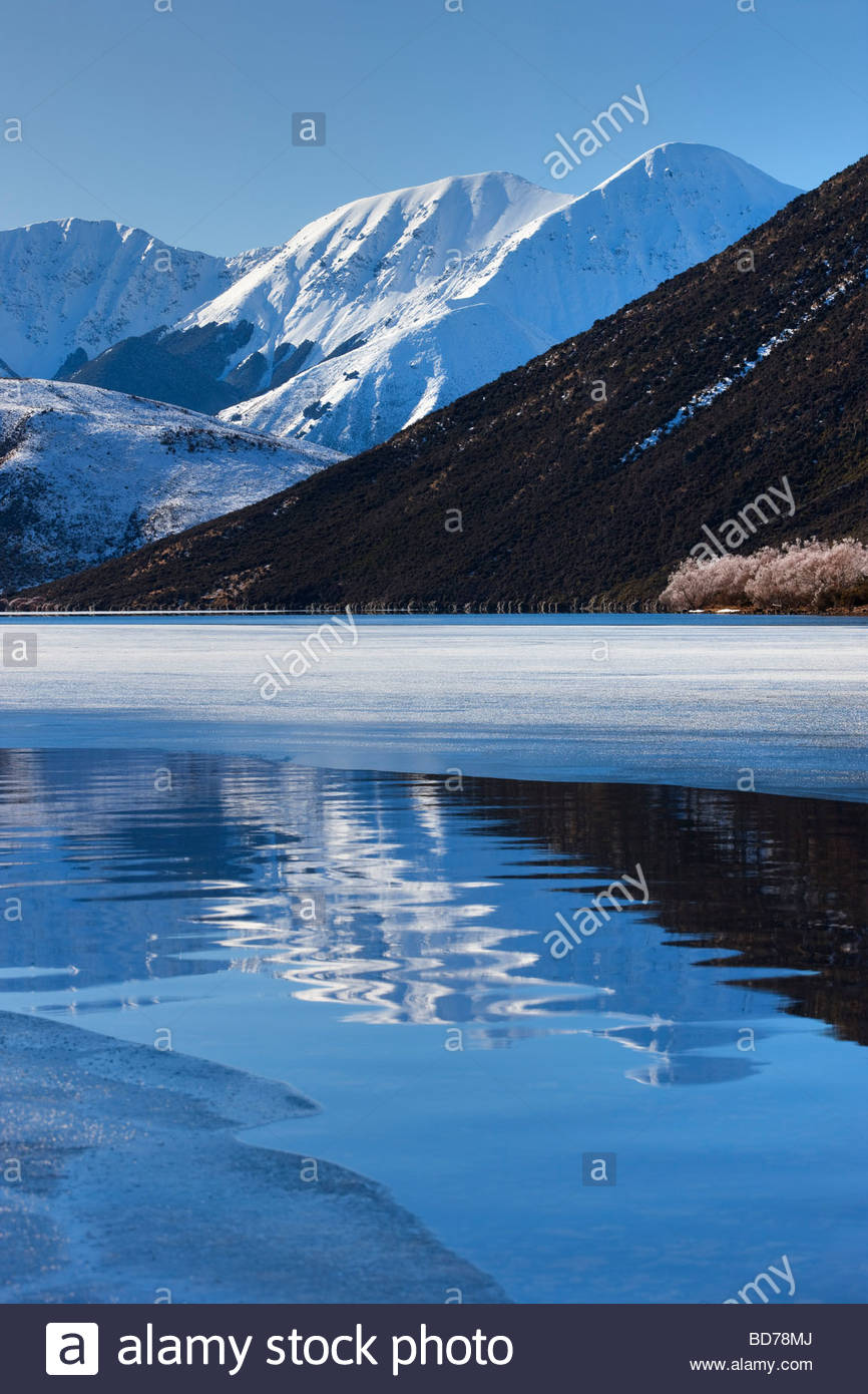 The mountain known as Sugar Loaf is reflected in a crack in the ice on Lake Pearson near Arthur's Pass, New - Stock Image