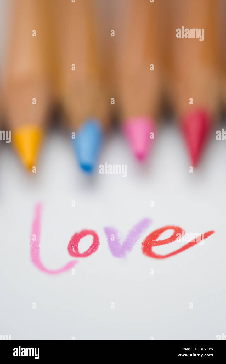 Coloured love word on paper and colouring pencils - Stock Image